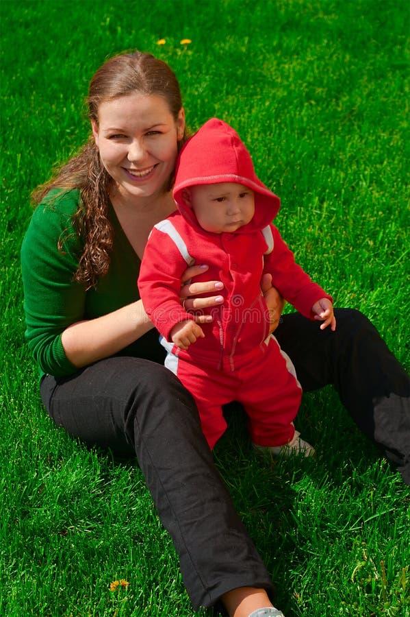 Het jonge meisje en haar kind zitten op het groene gras stock afbeeldingen