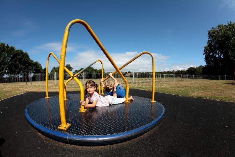 Het jonge meisje en jongens spelen op rotonde stock fotografie