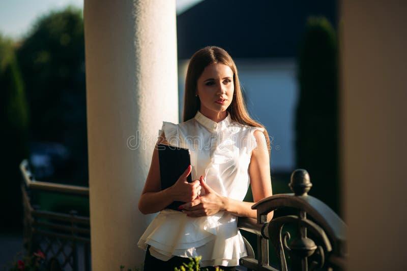 Het jonge meisje gebruikt een tablet voor het werk Vrouwelijke greep een tablet in handen De mooie vrouw be?indigt het werk royalty-vrije stock fotografie