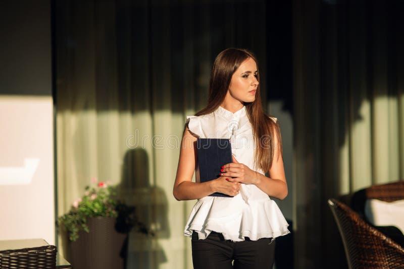 Het jonge meisje gebruikt een tablet voor het werk Vrouwelijke greep een tablet in handen De mooie vrouw be?indigt het werk royalty-vrije stock afbeelding