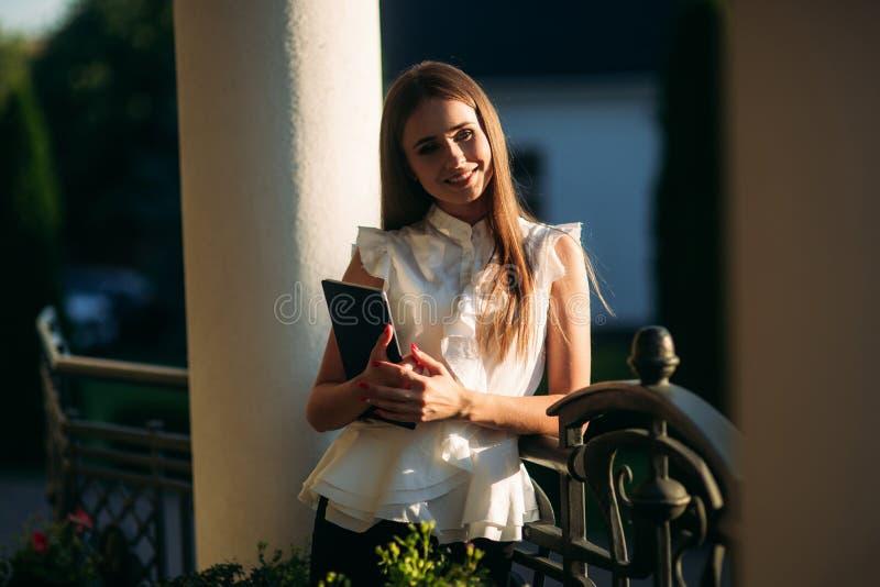 Het jonge meisje gebruikt een tablet voor het werk Vrouwelijke greep een tablet in handen De mooie vrouw be?indigt het werk stock afbeeldingen