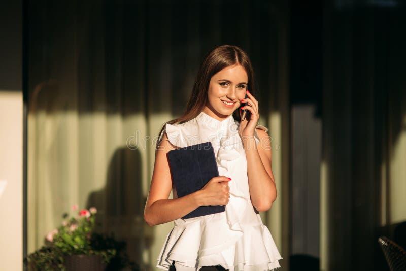 Het jonge meisje gebruikt een tablet voor het werk Vrouwelijke greep een tablet in handen De mooie vrouw be?indigt het werk royalty-vrije stock foto's