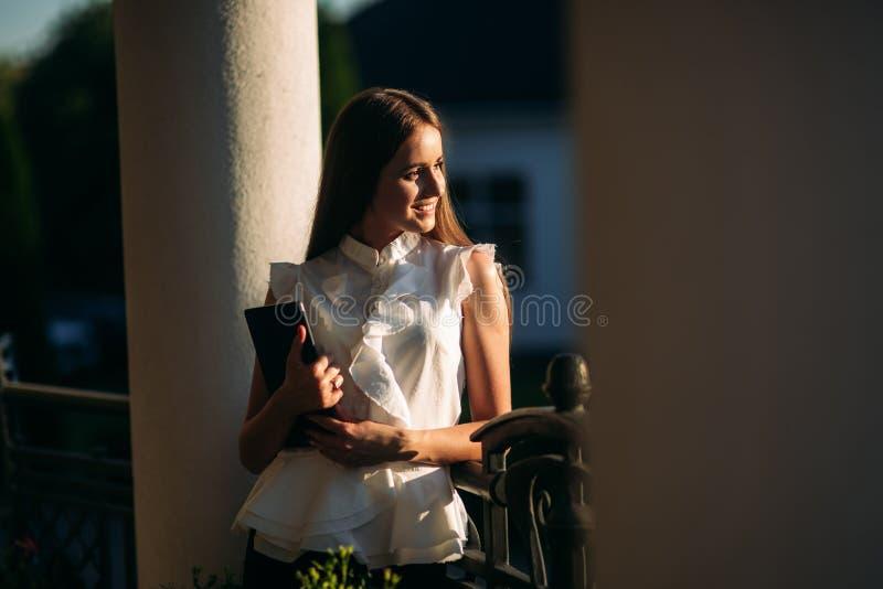 Het jonge meisje gebruikt een tablet voor het werk Vrouwelijke greep een tablet in handen De mooie vrouw be?indigt het werk royalty-vrije stock foto
