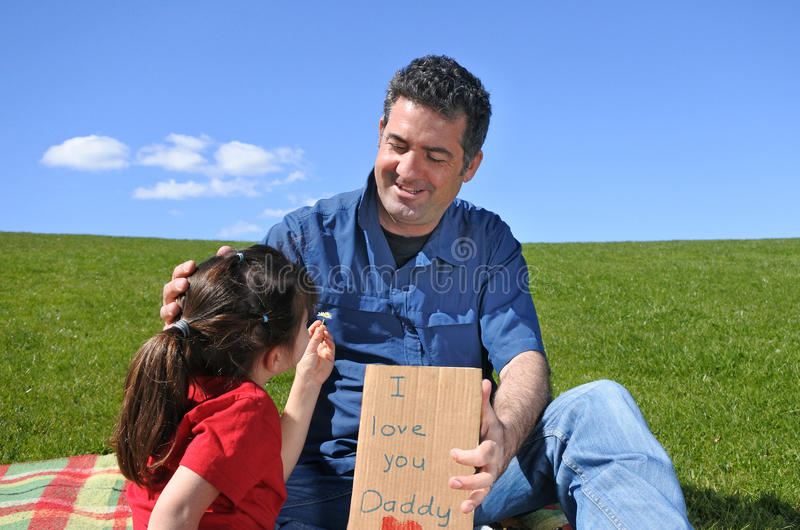 Het jonge meisje geeft haar vaderbloem en een kaart stock foto's