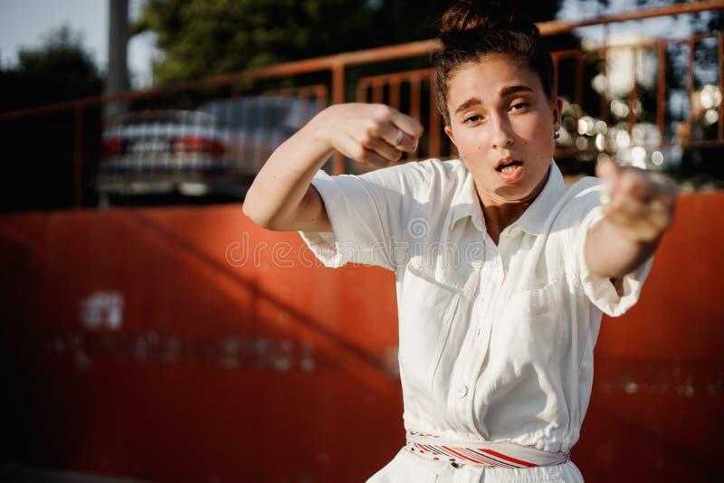 Het jonge meisje gekleed in wit overhemd is het dansen moderne dans in de straat op de achtergrond van parkeren in de zonnige dag royalty-vrije stock afbeelding