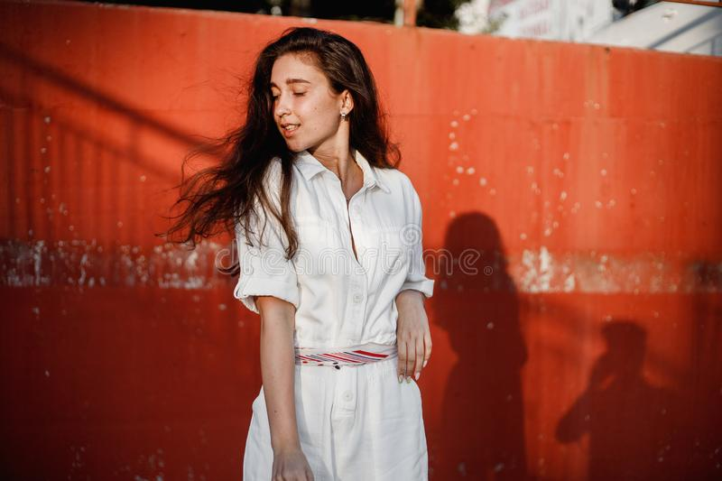 Het jonge meisje gekleed in wit overhemd stelt in de straat gainst een geschilderde concrete muur in de zonnige dag stock fotografie