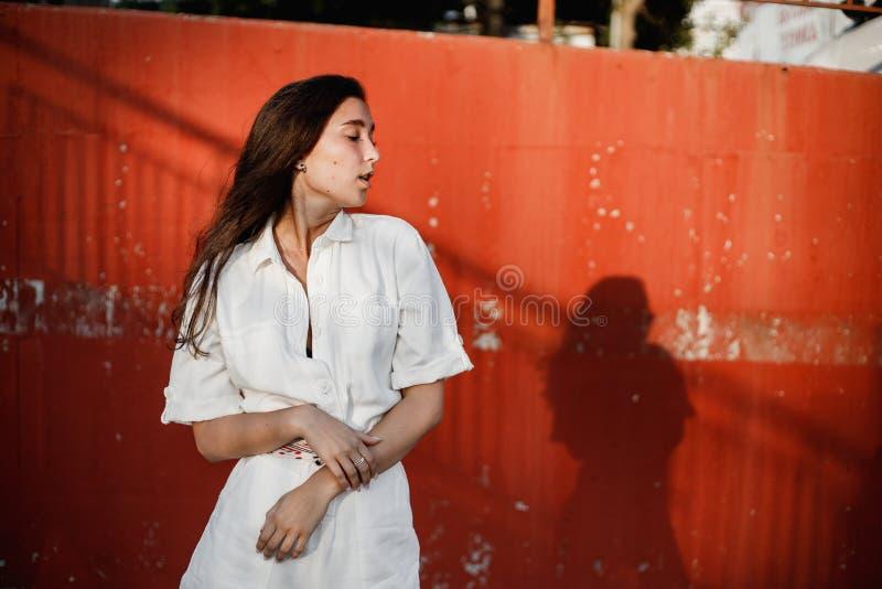 Het jonge meisje gekleed in wit overhemd stelt in de straat gainst een geschilderde concrete muur in de zonnige dag royalty-vrije stock foto's
