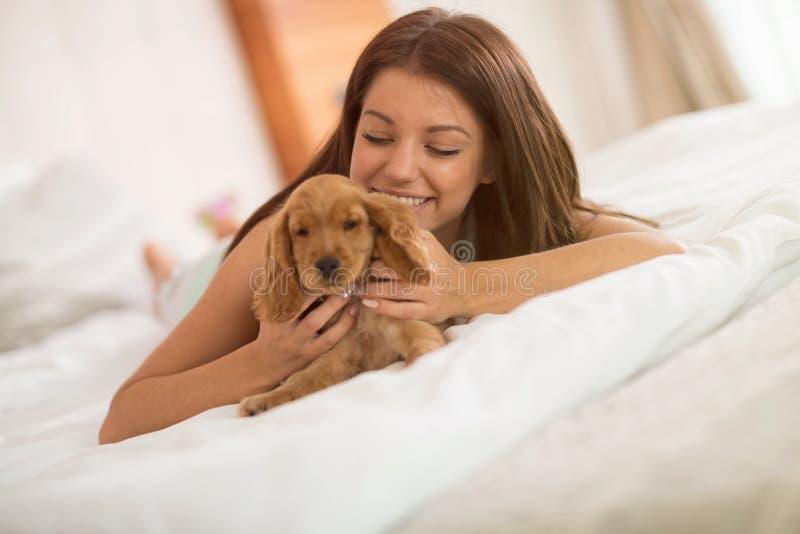 Het jonge meisje geniet van met haar puppy in slaapkamer royalty-vrije stock afbeelding