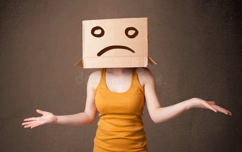Het jonge meisje gesturing met bruine kartondoos op haar hoofd met s stock fotografie
