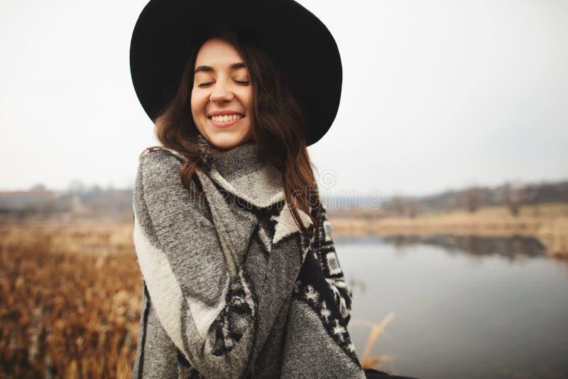 Het jonge meisje in grijze cardigan en zwarte hoed glimlacht en stelt op de kust van een meer royalty-vrije stock afbeeldingen