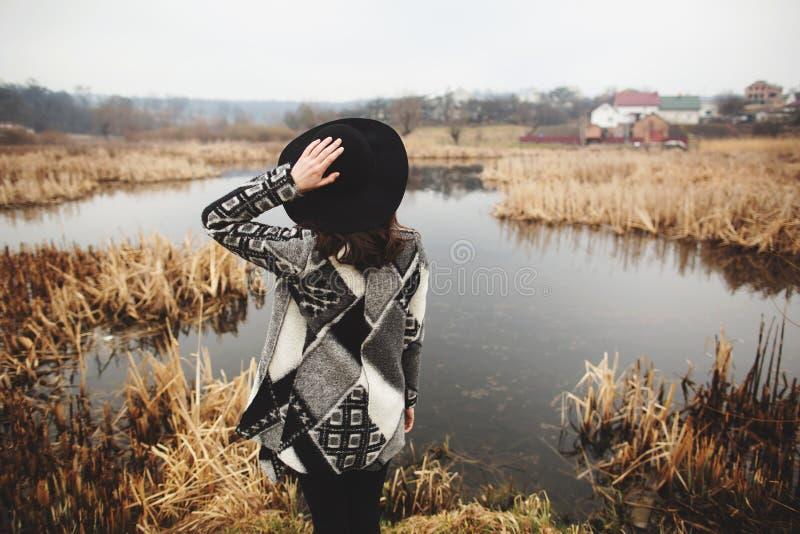 Het jonge meisje in grijze cardigan stelt op de kust van een meer Achter mening royalty-vrije stock fotografie