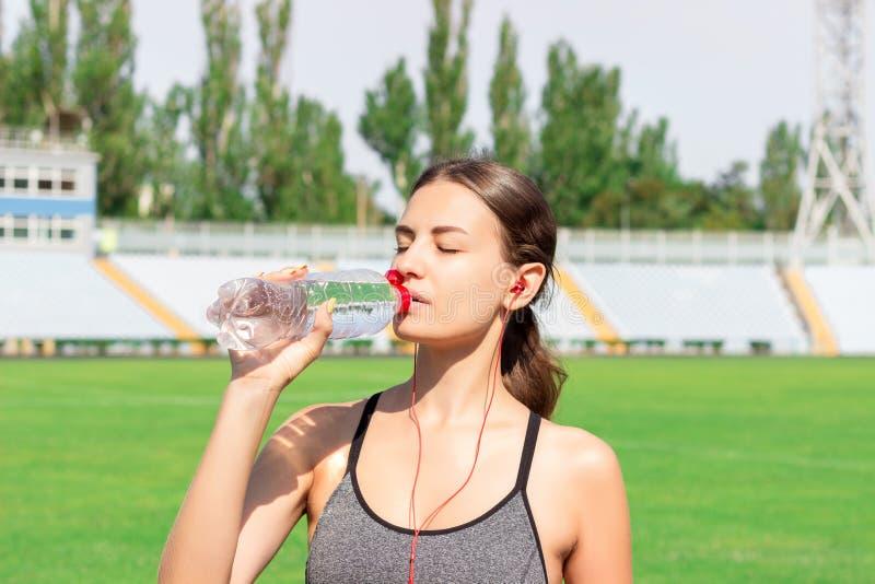 Het jonge meisje in grijze sportkleding drinkt water en het luisteren muziek na het teaining vrouw die en zich met fles bij stadi stock foto
