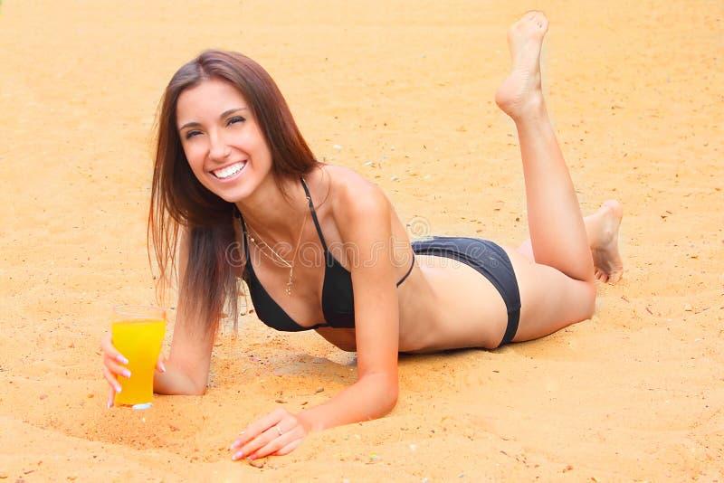 Het jonge meisje heeft een rust op een houten strand stock fotografie