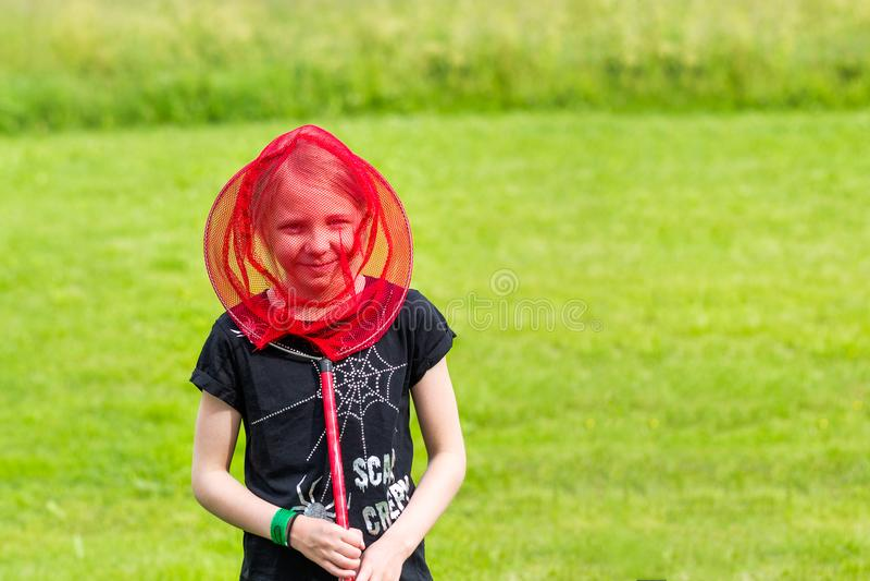 Het jonge meisje heeft pret met een vlinder netto op de weide royalty-vrije stock afbeeldingen