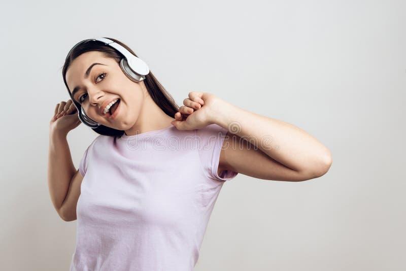 Het jonge meisje in hoofdtelefoons geniet van luister aan muziek royalty-vrije stock fotografie