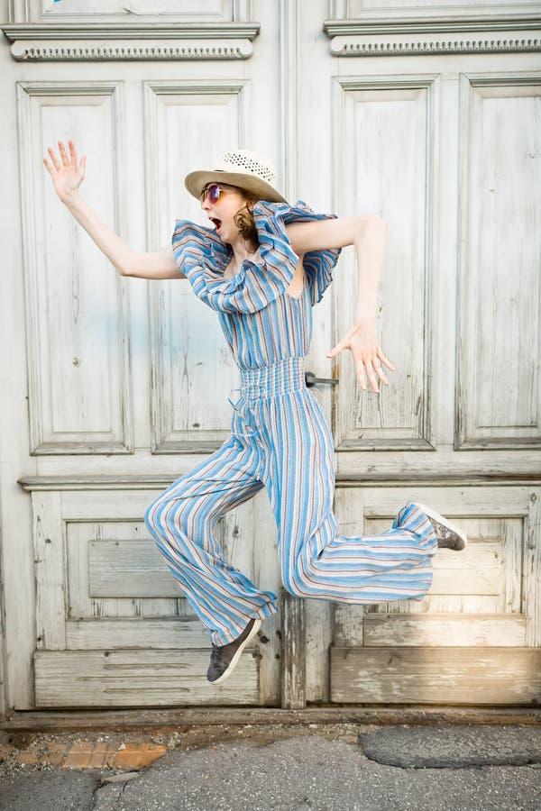 Het jonge meisje in jumpsuit springt bij roestige uitstekende poort stock foto's