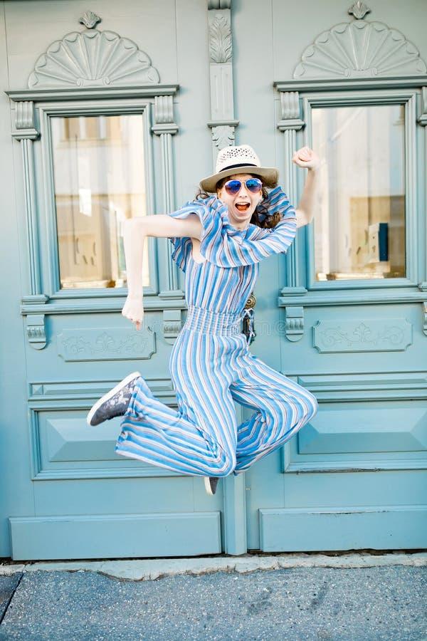 Het jonge meisje in jumpsuit springt bij uitstekende poort stock afbeelding