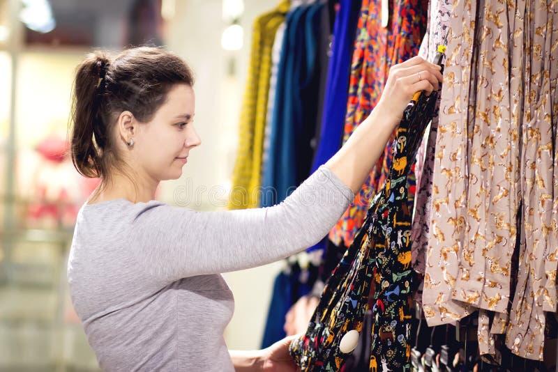 Het jonge meisje kiest blouse in kledingsopslag Jonge Kaukasische vrouw bij het winkelen Het concept van kledingskleren Het kopen royalty-vrije stock foto's