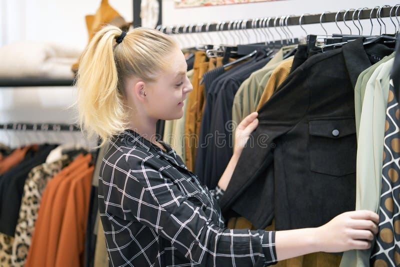 Het jonge meisje kiest dingen in een kledingsopslag stock afbeeldingen