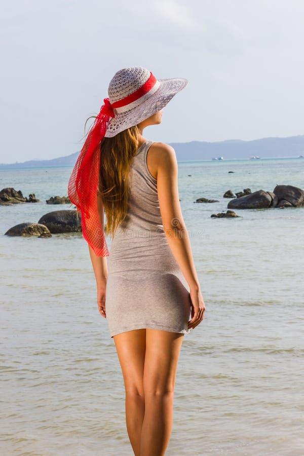 Het jonge meisje kijkt aan het overzees in de hoed royalty-vrije stock afbeelding
