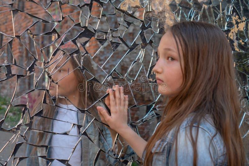 Het jonge meisje kijkt in een gebroken spiegel en toont haar hand op een spiegel Problemen van adolescenten Overgangsleeftijd stock foto's