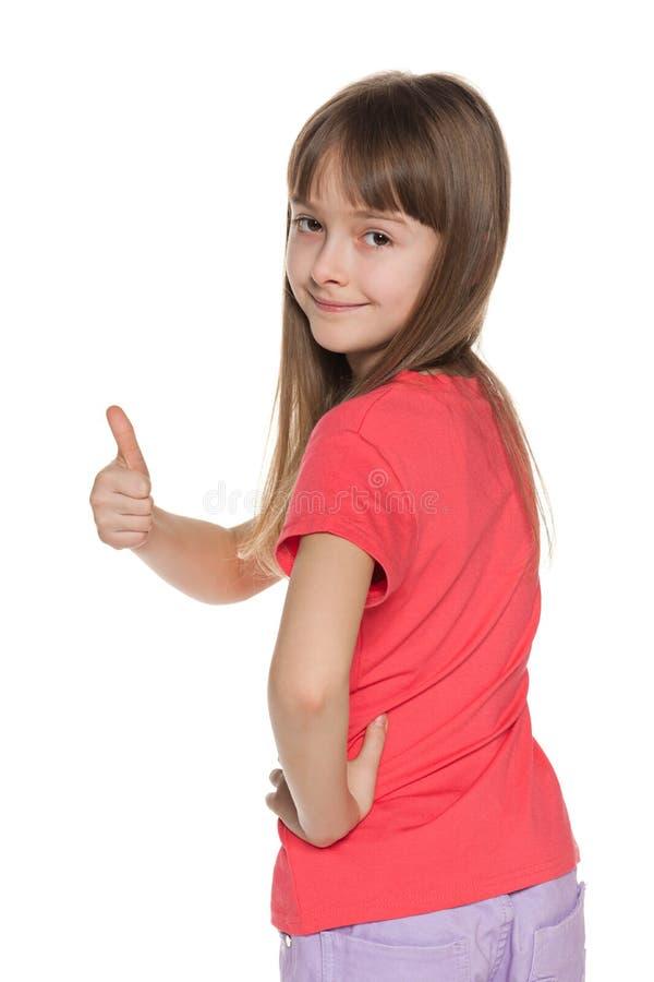 Het jonge meisje kijkt terug en houdt haar duim tegen stock fotografie