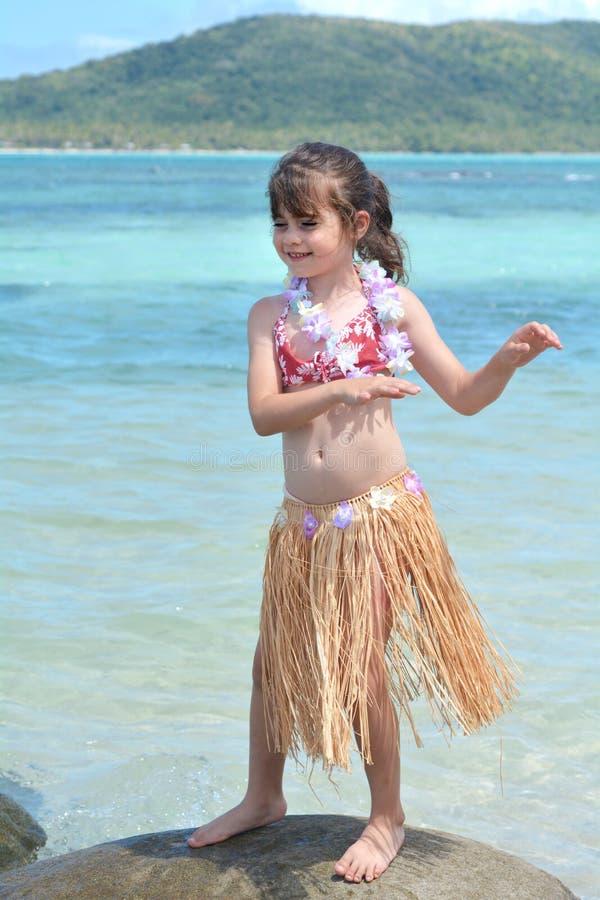 Het jonge meisje kleedde zich omhoog als dans van het hulameisje tegen blauwe lagune a stock foto's