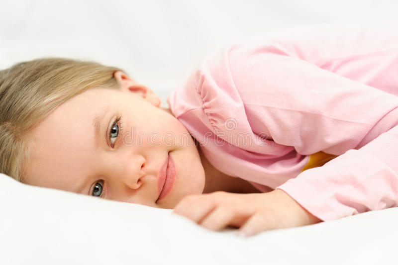 Het jonge meisje legt op bed met vreedzame gezichtsuitdrukking stock fotografie