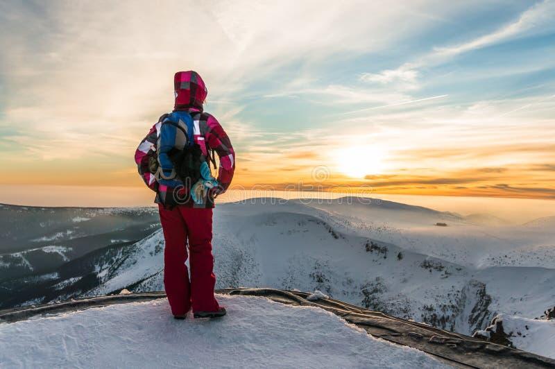 Het jonge meisje letten op bij de zonsondergang op de bovenkant van bergen stock afbeelding