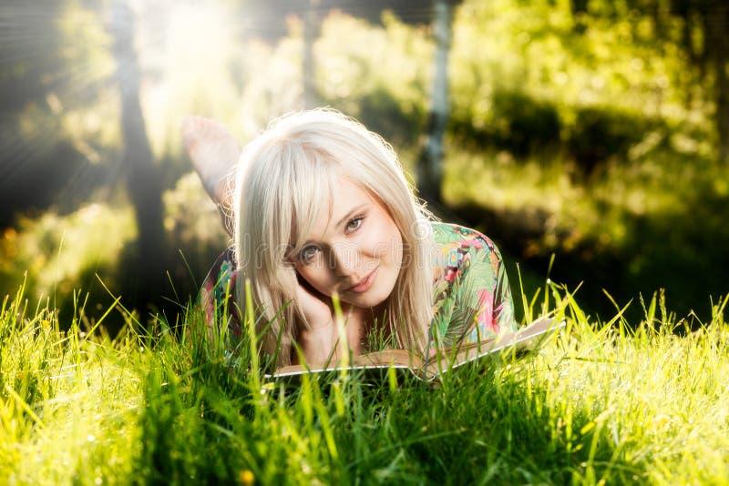 Het jonge meisje ligt op groen gras en leest boek royalty-vrije stock foto's