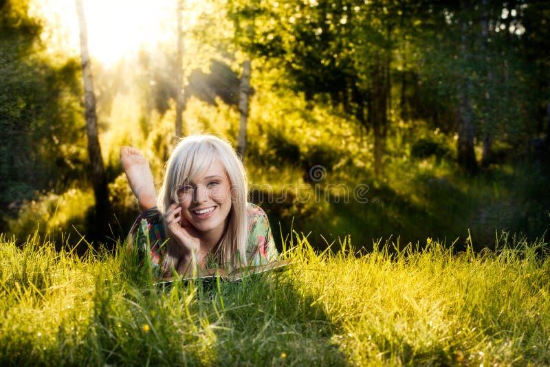 Het jonge meisje ligt op groen gras en leest boek royalty-vrije stock afbeelding