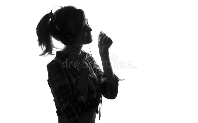 Het jonge meisje luisteren aan muziek op hoofdtelefoons en zingt stock afbeeldingen