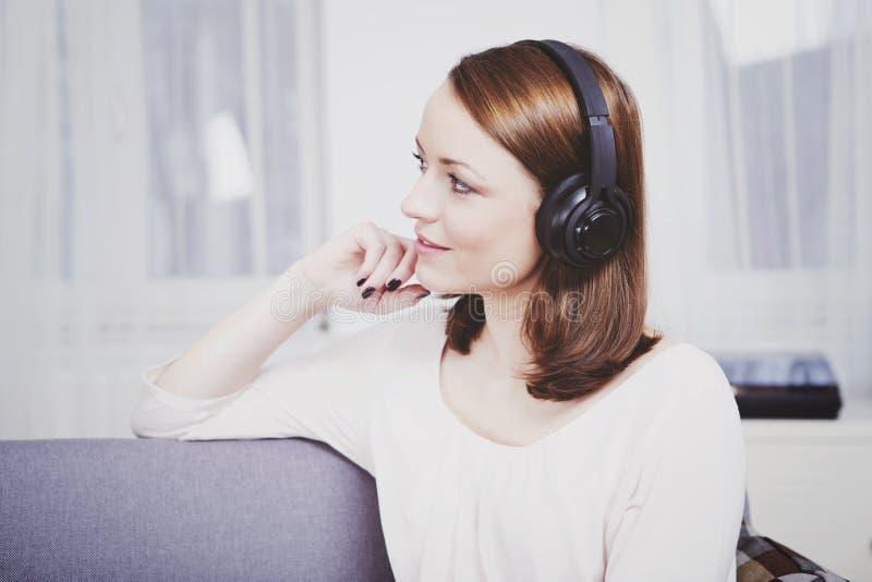 Het jonge meisje luistert aan muziek met hoofdtelefoons stock afbeeldingen