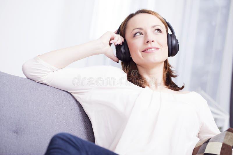 Het jonge meisje luistert aan muziek met hoofdtelefoons royalty-vrije stock afbeeldingen