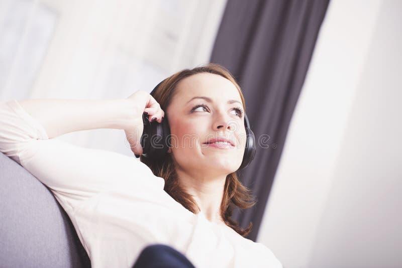 Het jonge meisje luistert aan muziek met hoofdtelefoons royalty-vrije stock foto's