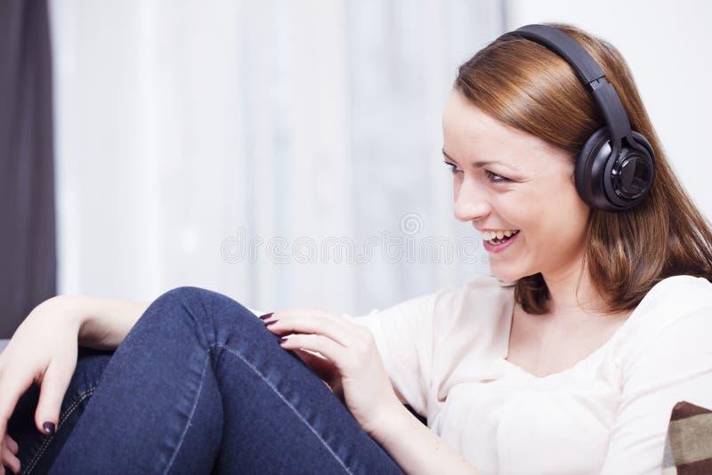 Het jonge meisje luistert aan muziek met hoofdtelefoons stock fotografie