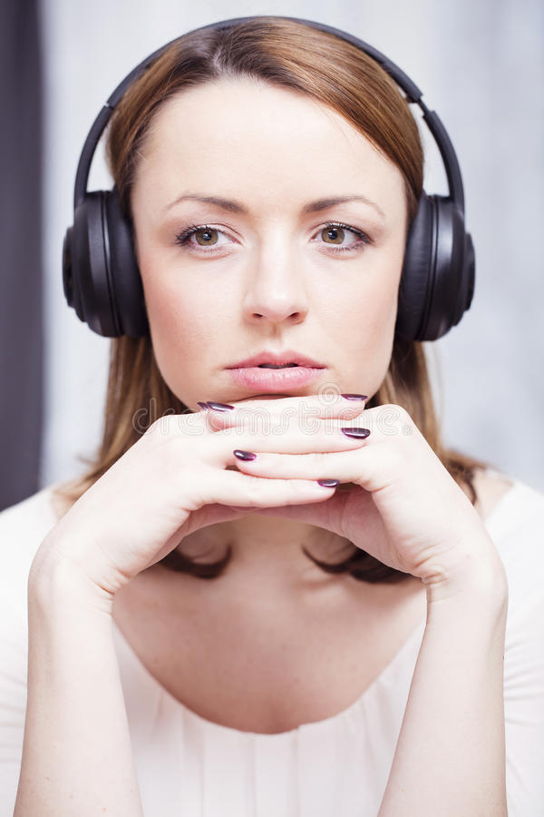 Het jonge meisje luistert aan muziek met hoofdtelefoons stock afbeelding