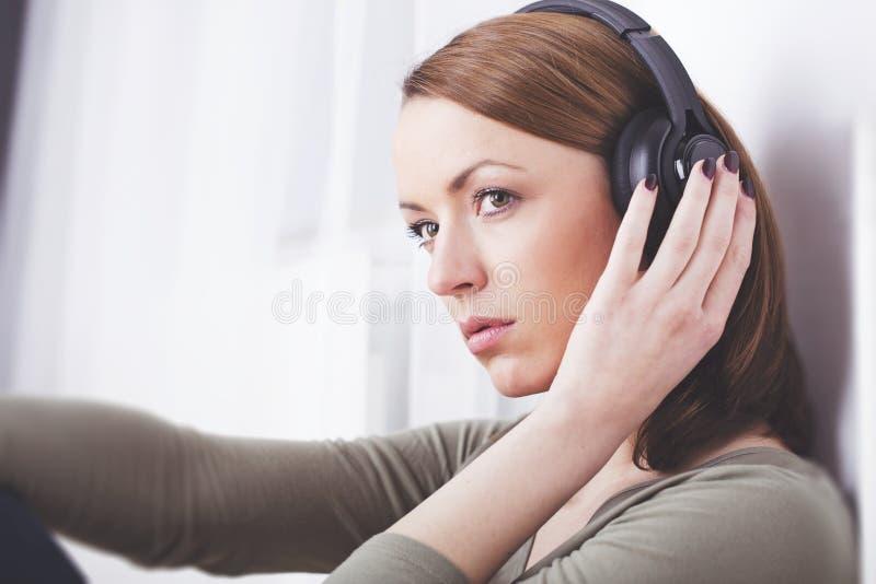 Het jonge meisje luistert aan muziek met hoofdtelefoons royalty-vrije stock afbeelding