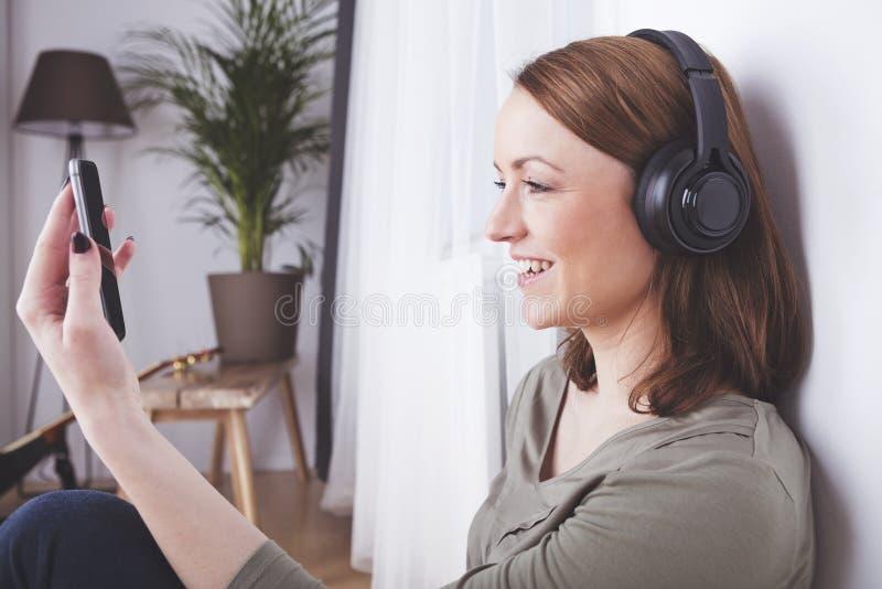 Het jonge meisje luistert aan muziek met hoofdtelefoons stock foto's
