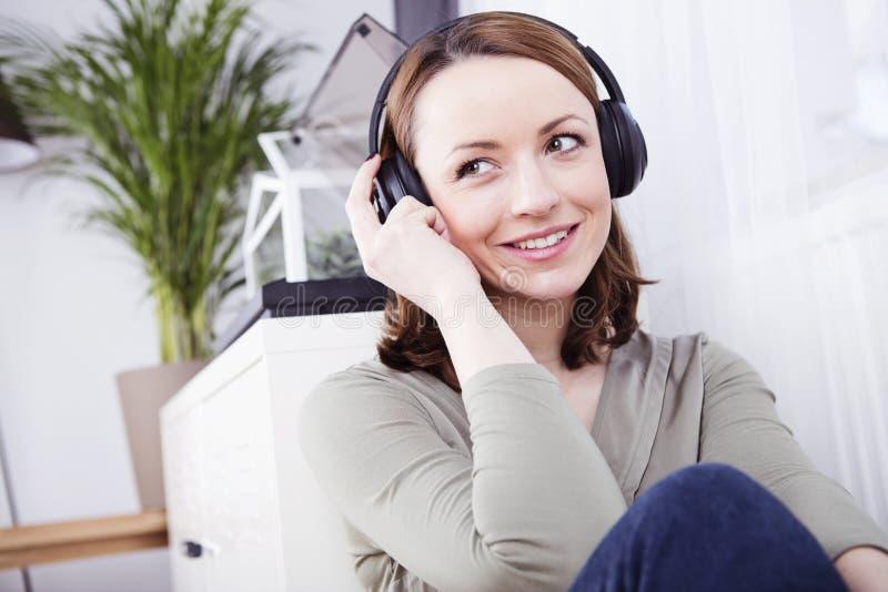 Het jonge meisje luistert aan muziek met hoofdtelefoons stock foto