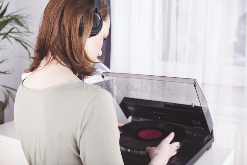 Het jonge meisje luistert aan muziek met hoofdtelefoons royalty-vrije stock fotografie