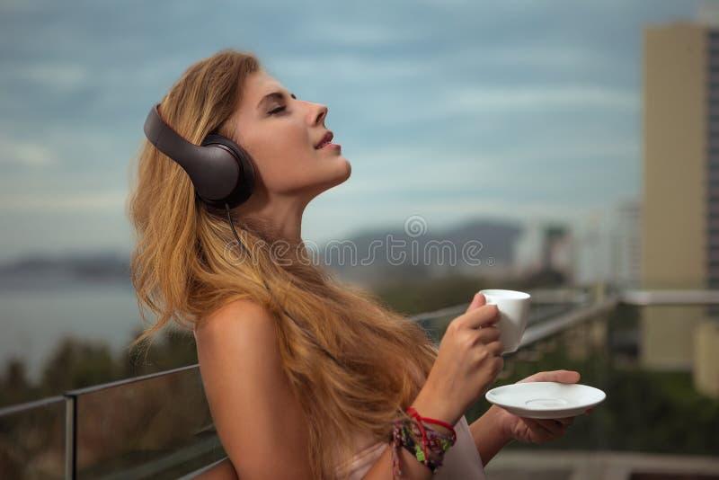 Het jonge meisje luistert aan muziek van hoofdtelefoons en zit  royalty-vrije stock afbeeldingen