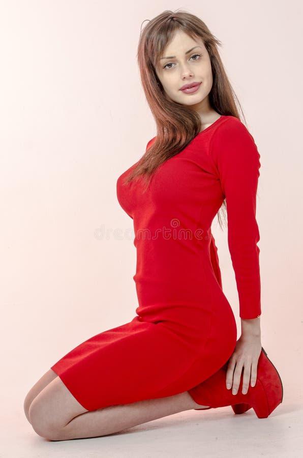 Het jonge meisje met een mooi cijfer in een in rode kleding in nauwsluitende miniskirt en rood hoog hielen en platform kleedde zi stock foto