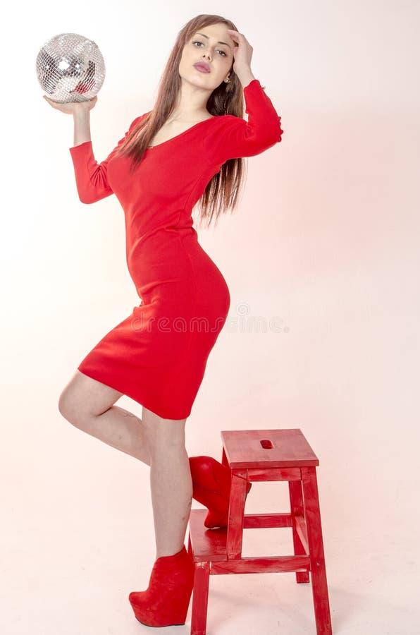 Het jonge meisje met een mooi cijfer in een in rode kleding in nauwsluitende miniskirt en rood hoog hielen en platform kleedde zi stock afbeeldingen