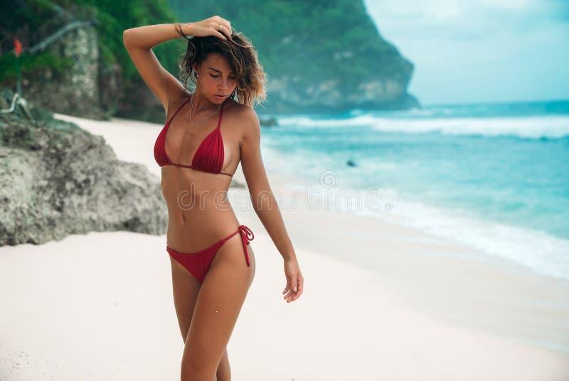 Het jonge meisje met een schitterend lichaam rust op het strand met wit zand dichtbij de oceaan Mooi sexy model in een rood royalty-vrije stock afbeeldingen
