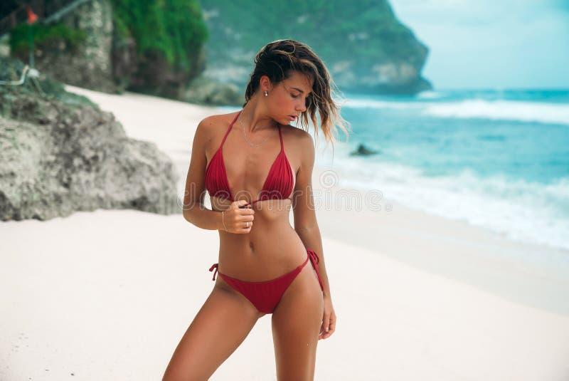 Het jonge meisje met een schitterend lichaam rust op het strand met wit zand dichtbij de oceaan Mooi sexy model in een rood stock foto's