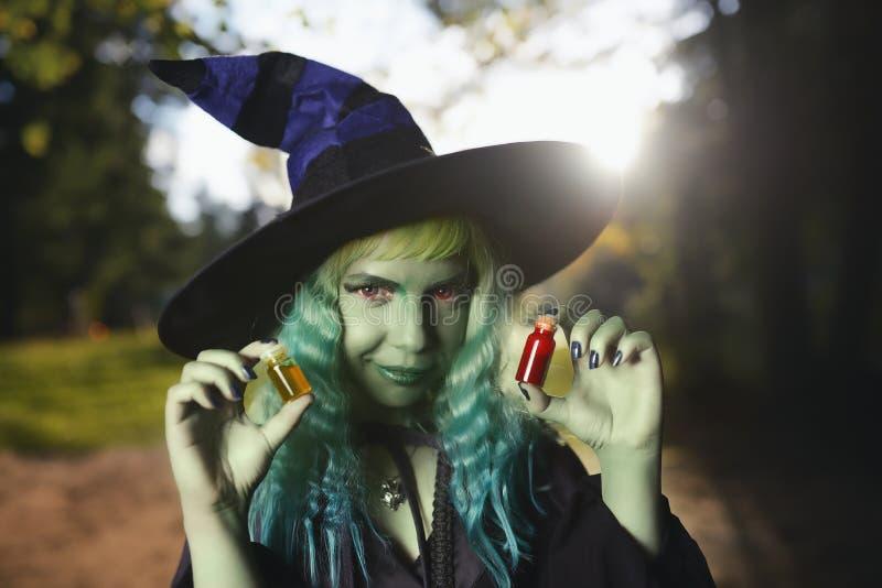 Het jonge meisje met groen haar en huidkostuum van heks in bos houdt kleine flessen met rood en oranje drankje Halloween-tijd stock afbeelding