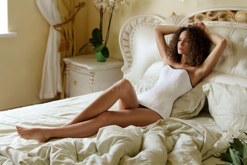 Het jonge meisje met krullend haar die op een bed met verfomfaaid bed in een wit korset liggen en onderzoekt de afstand in beauti royalty-vrije stock fotografie