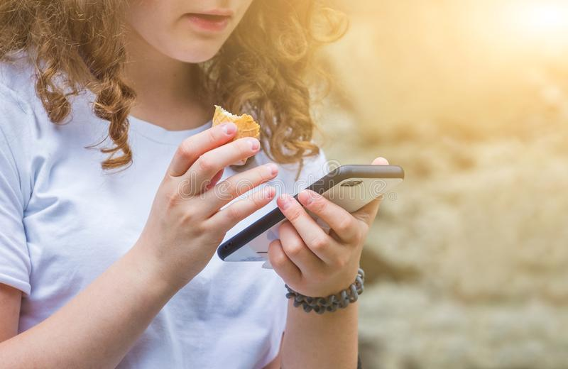 Het jonge meisje met krullend haar houdt een telefoon in haar hand en eet roomijs in de stralen van de zon Vakantie in summer_ royalty-vrije stock afbeelding