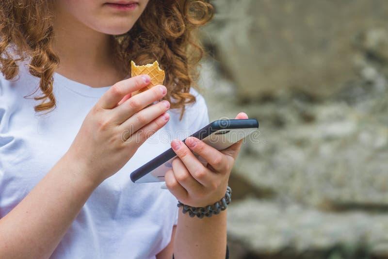 Het jonge meisje met krullend haar houdt een telefoon in haar hand en eet roomijs Vakantie in summer_ royalty-vrije stock foto
